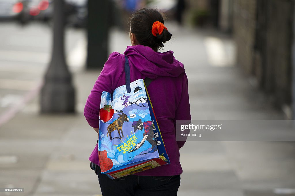 A customer carries a Trader Joe's Co. shopping bag in San Francisco, California, U.S., on Friday, Sept. 13, 2013. Trader Joe's Co., the closely held grocery store chain, will end health benefits for part-time workers next year, directing them instead to anew insurance marketplaces as companies revamp medical coverage to fit the U.S. Affordable Care Act. Photographer: David Paul Morris/Bloomberg via Getty Images