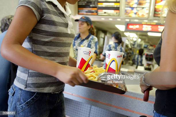 A customer carries a tray of food at McDonald's June 19 2003 in Miami Florida News reports say that In response to warnings that use of antibiotics...