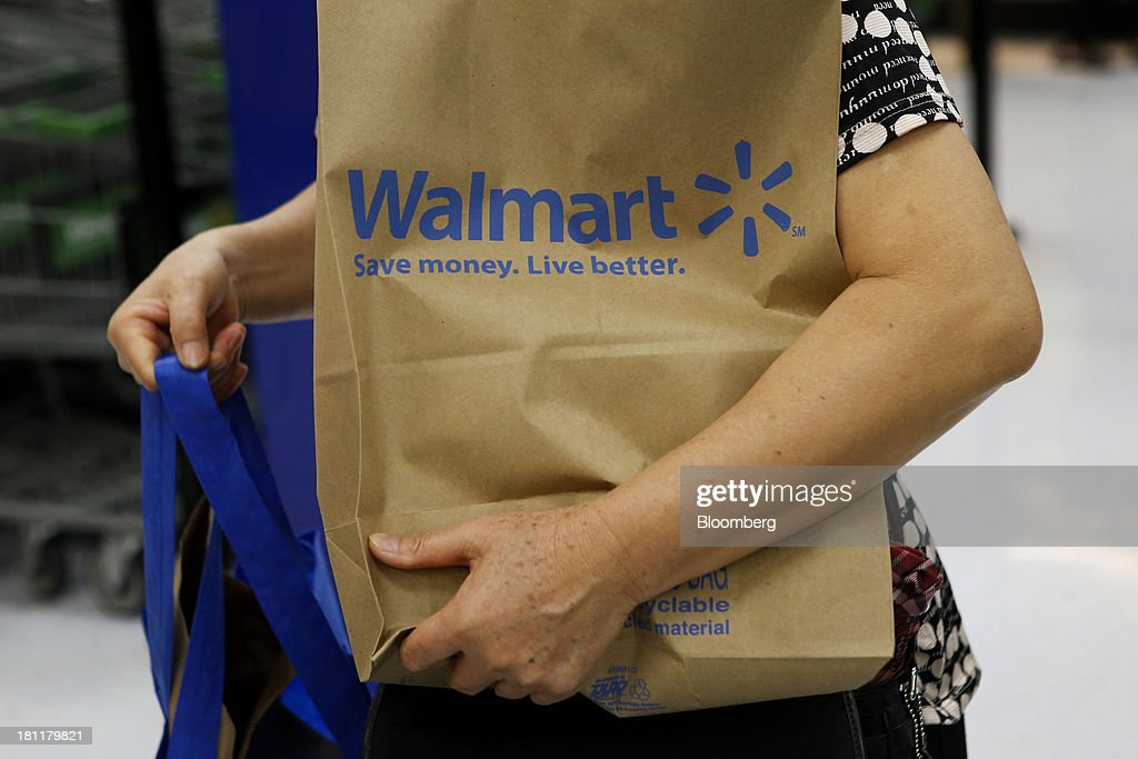 A customer carries a Walmart paper shopping bag during the grand opening of a Wal-Mart Stores Inc. location in the Chinatown neighborhood of Los Angeles, California, U.S., on Thursday, Sept. 19, 2013. Wal-Mart Stores Inc. will phase out 10 chemicals it sells in favor of safer alternatives and disclose the chemicals contained in four product categories, the company announced Sept. 12.Photographer: Patrick T. Fallon/Bloomberg via Getty Images