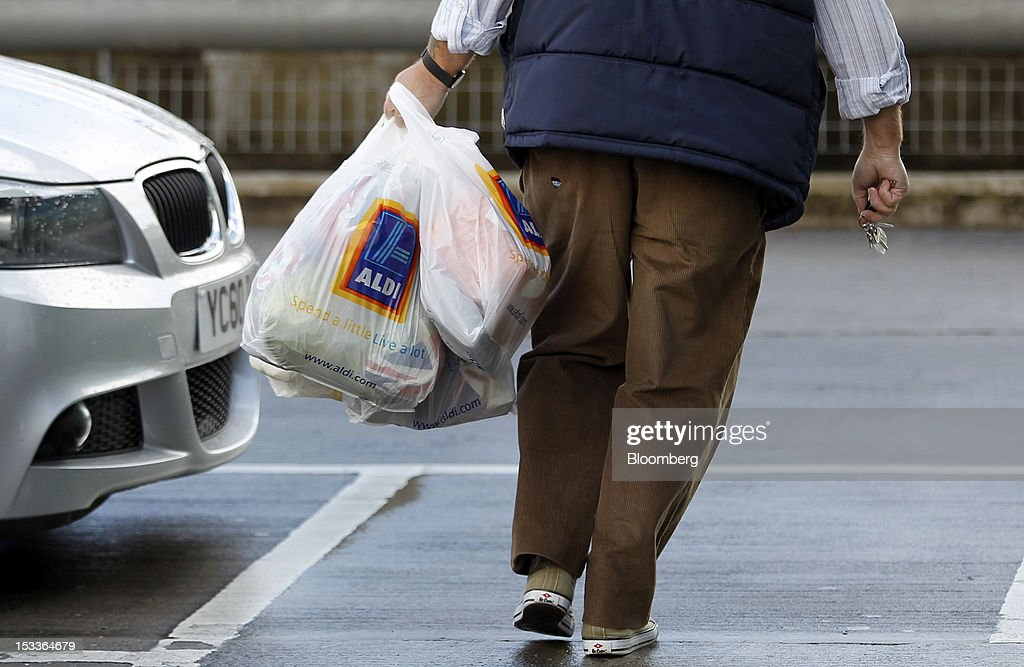 A customer carries Aldi branded shopping bags as he leaves a supermarket operated by Aldi Group, Germany's biggest discount-food retailer, in this arranged photograph in Manchester, U.K., on Thursday, Oct. 4, 2012. U.K. shop-price inflation slowed in September as retailers offered discounts to attract cash-strapped consumers, the British Retail Consortium said. Photographer: Paul Thomas/Bloomberg via Getty Images