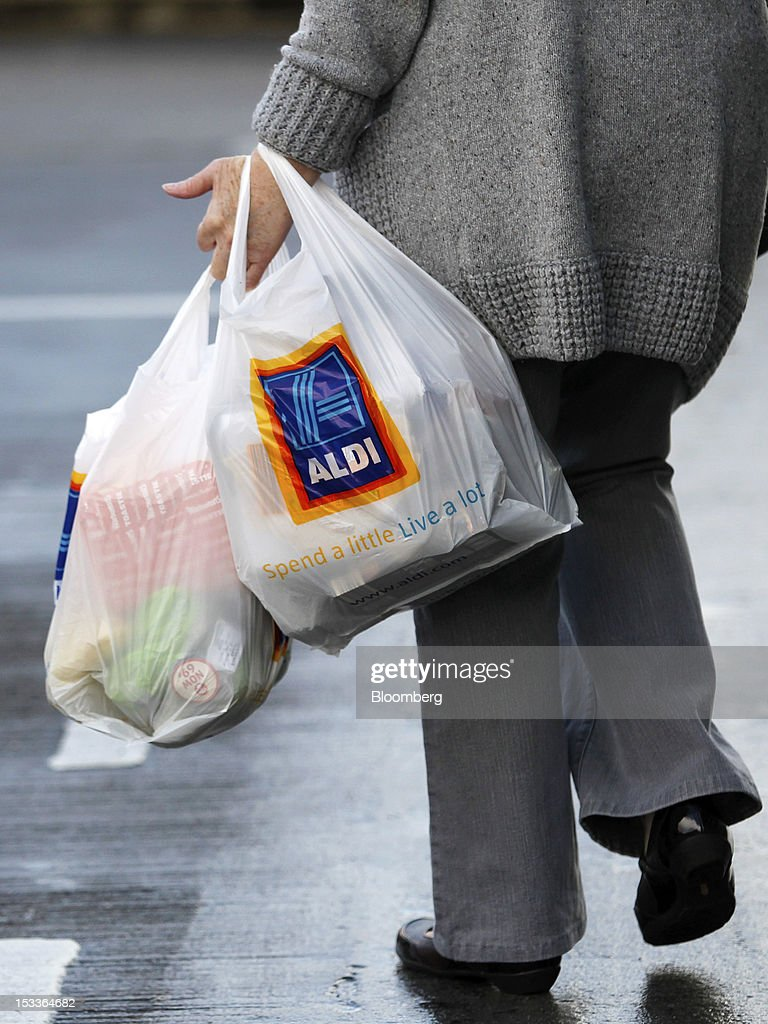 A customer carries Aldi branded shopping bags as she leaves a supermarket operated by Aldi Group, Germany's biggest discount-food retailer, in this arranged photograph in Manchester, U.K., on Thursday, Oct. 4, 2012. U.K. shop-price inflation slowed in September as retailers offered discounts to attract cash-strapped consumers, the British Retail Consortium said. Photographer: Paul Thomas/Bloomberg via Getty Images