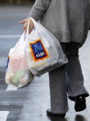 A customer carries Aldi branded shopping bags as she leaves a supermarket operated by Aldi Group Germany's biggest discountfood retailer in this...