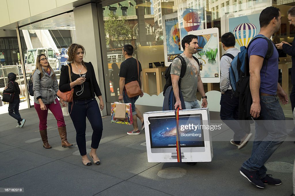A customer carries an Apple Inc. computer in front of an Apple Inc. store in San Francisco, California, U.S., on Friday, April 19, 2013. Apple Inc. is expected to release earnings data on April 23. Photographer: David Paul Morris/Bloomberg via Getty Images