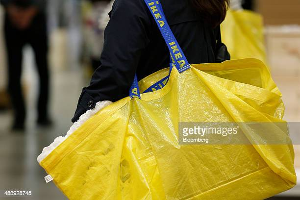 A customer carries an Ikea shopping bag as she shops at an Ikea store in Tokyo Japan on Thursday April 10 2014 Ikea the world's largest...