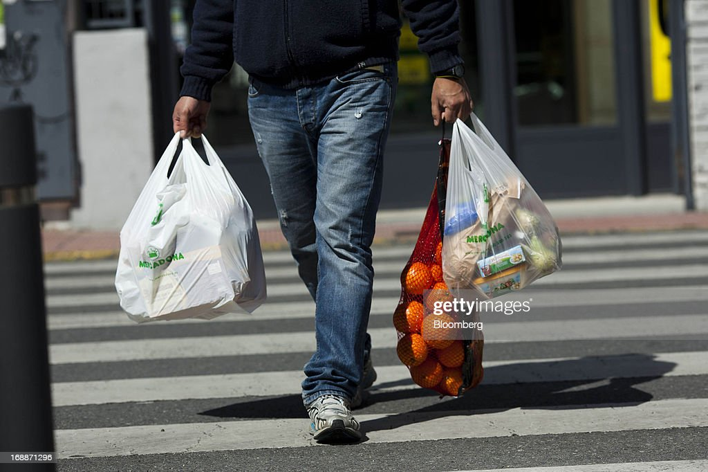 A customer carries bags of produce and oranges after shopping at a Mercadona supermarket in Madrid, Spain, on Thursday, May 16, 2014. Billionaires Juan Roig and Hortensia Herrero, the husband-and-wife team that controls Mercadona SA, Spain's largest supermarket chain, created thousands of jobs last year as their country's economy crumbled. Photographer: Angel Navarrete/Bloomberg via Getty Images