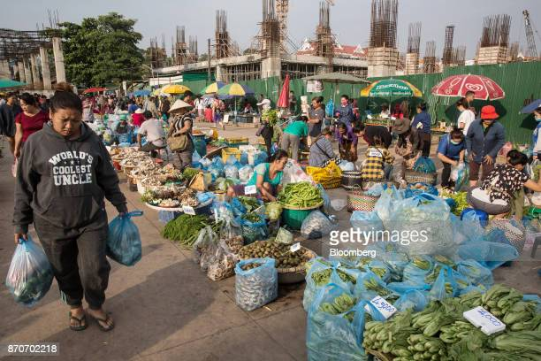 A customer carries bags of vegetables while walking past the vegetable vendors at a morning market in Vientiane Laos on Thursday Nov 2 2017 Located...