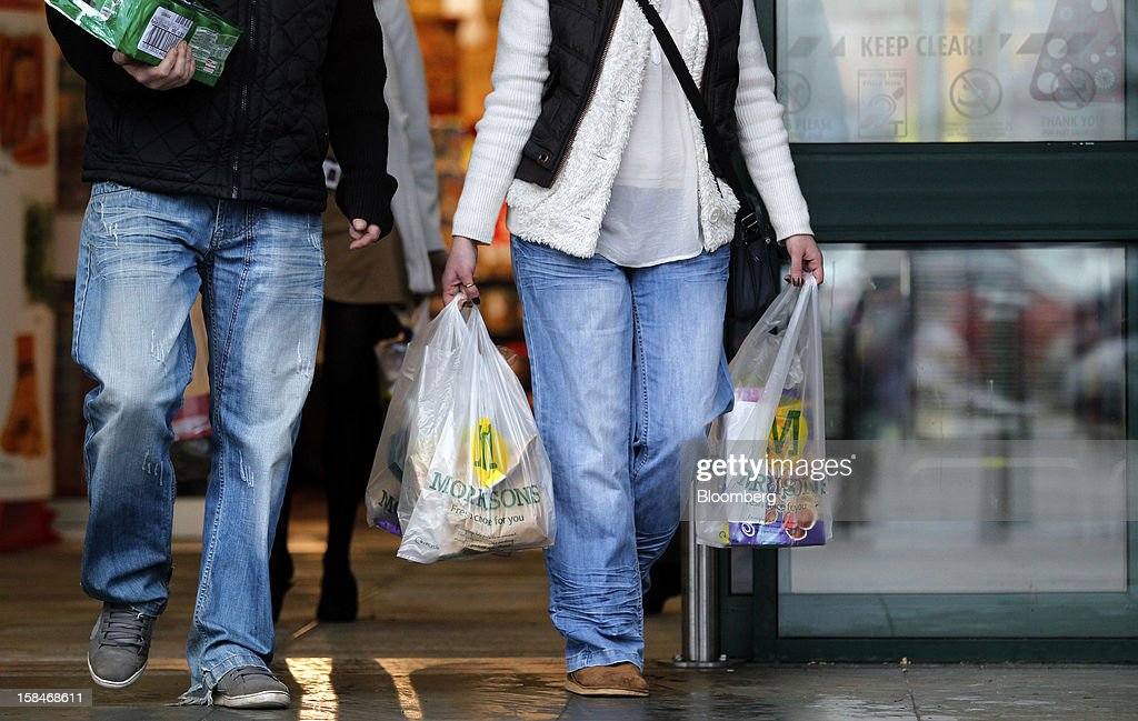 A customer carries branded shopping bags as she exits a Morrisons supermarket, operated by William Morrisons Supermarkets Plc, in Chadderton, U.K., on Monday, Dec. 17, 2012. The British Christmas is the biggest epicurean occasion of the year, with households spending a total of 4 billion pounds on food in the final week before Dec. 25. Photographer: Paul Thomas/Bloomberg via Getty Images