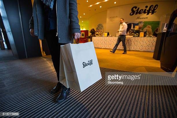 A customer carries branded Steiff bags as they leave the gift shop at the Steiff GmbH stuffed toy factory in Giengen Germany on Tuesday March 1 2016...