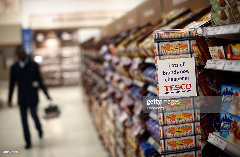 A customer carries goods in a shopping basket as he walks past the bread display inside a Tesco supermarket store operated by Tesco Plc in the...