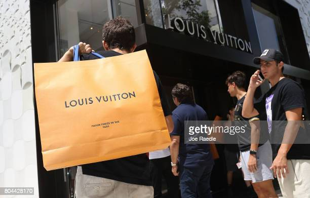 A customer carries his Louis Vuitton bag from the store where they are selling limited edition supreme and Louis Vuitton collaboration items on June...