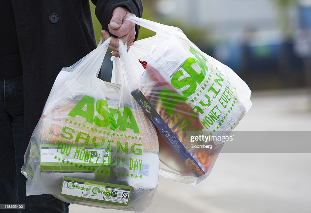 A customer carries his purchases in branded shopping bags after leaving an Asda supermarket store, operated by Wal-Mart Stores Inc., in the Merton borough of London, U.K., on Monday, May 13, 2013. Asda, the U.K. supermarket chain owned by Wal-Mart Stores Inc., said sales rose 4.5 percent last year and it's investing 700 million pounds ($1 billion) into stores and online operations. Photographer: Jason Alden/Bloomberg via Getty Images