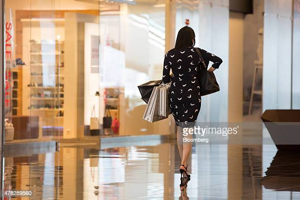 A customer carries shopping bags after shopping at the Esentai luxury shopping mall in Almaty Kazakhstan on Tuesday June 23 2015 Kazakhstan completed...