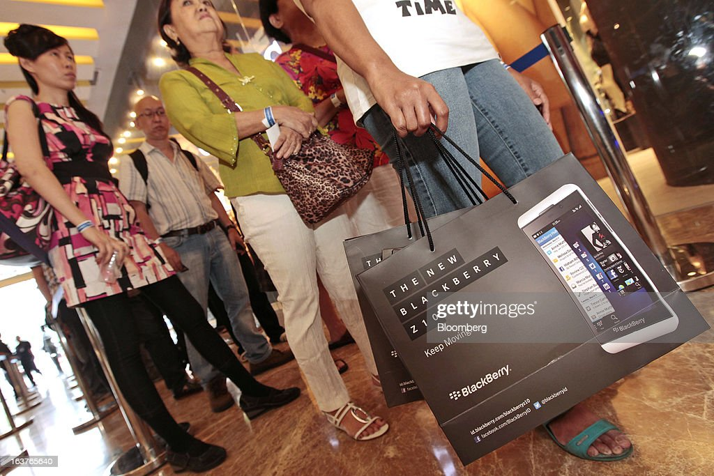 A customer carries shopping bags featuring the BlackBerry Z10 smartphone during the consumer launch of the device at the Central Park Mall in Jakarta, Indonesia, on Friday, March 15, 2013. BlackBerry, the Canadian smartphone maker that rolled out a new lineup in January, said one of its 'established partners' is buying 1 million BlackBerry 10 phones, the biggest order in the company's history. Photographer: Dimas Ardian/Bloomberg via Getty Images