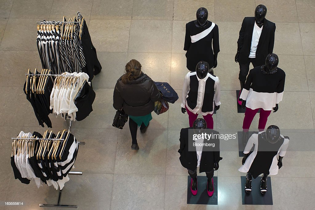 A customer carries shopping bags past clothes mannequins inside a Zara fashion store, operated by Inditex SA, in Madrid, Spain, on Tuesday, March 12, 2013. Europe's richest man, Amancio Ortega, the 76-year-old founder of Inditex SA, the world's biggest clothing retailer and owner of the Zara clothing chain, is No. 3 on Standard & Poor's 500 Index with a net worth of $57.4 billion, $4.9 billion ahead of Warren Buffett, 82. Photographer: Angel Navarrete/Bloomberg via Getty Images