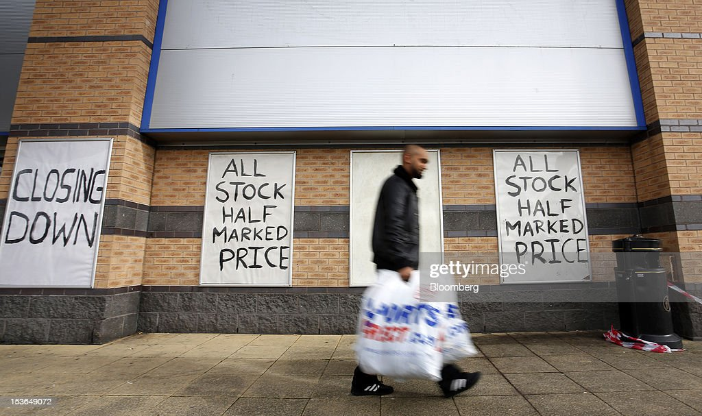 A customer carries Sports Direct International Plc branded shopping bags as he leaves a JJB Sports Plc store during a closing down sale in Rochdale, U.K., on Saturday, Oct. 6, 2012. JJB Sports Plc, a U.K. sporting goods retailer, will close most of its stores with the remaining 20 being acquired by competitor Sports Direct International Plc, according to a statement from KPMG LLP, which was appointed as administrator to the Wigan, England-based company. Photographer: Paul Thomas/Bloomberg via Getty Images