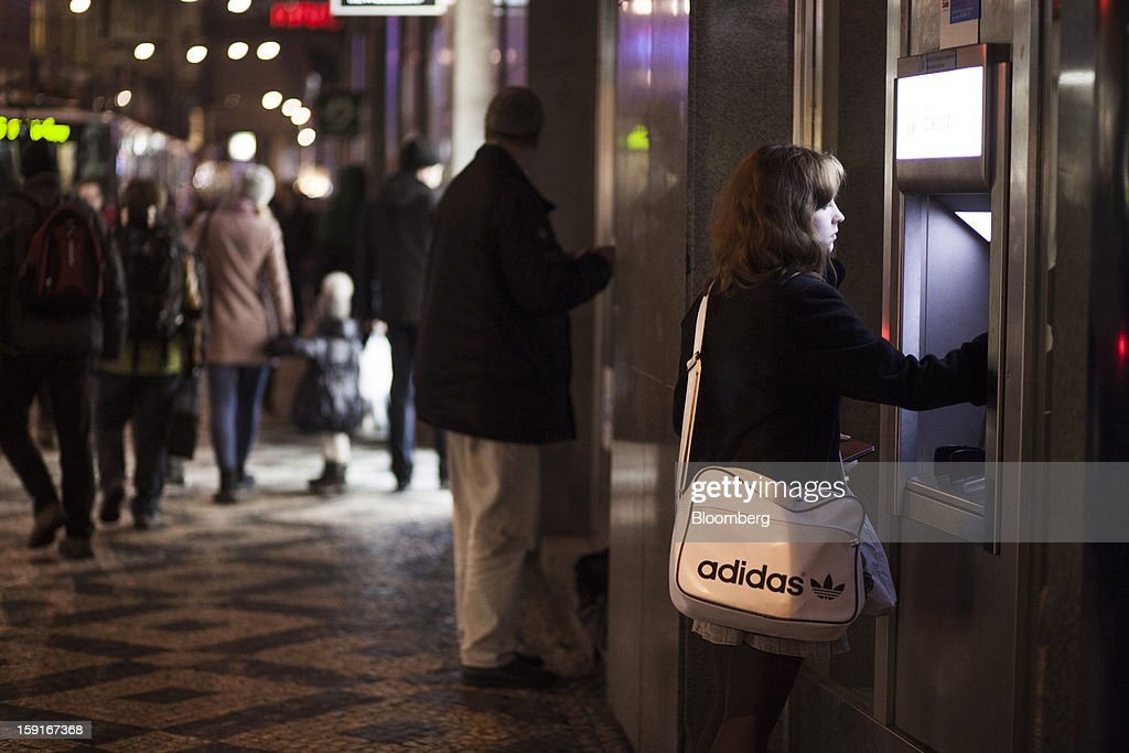 A customer carrying an Adidas AG-branded bag withdraws money from an automated teller machine (ATM) in Prague, Czech Republic, on Tuesday, Jan. 8, 2013. The Czech economy is showing weak domestic demand as households and businesses cut spending due to government austerity programs and the euro area's debt crisis. Photographer: Bartek Sadowski/Bloomberg via Getty Images