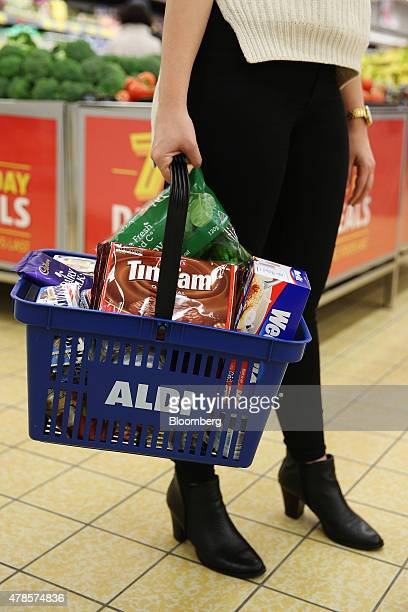 A customer carrying an Aldi Stores Ltd branded basket walks through one of the company's food stores in Sydney Australia on Thursday June 25 2015...