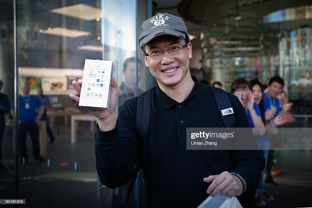 A customer celebrates buying the first new iPhone 5s at the Wangfujing flagship store on September 20, 2013 in Beijing, China. Apple launched the new iPhone 5C model that will run iOS 7 is made from hard-coated polycarbonate and comes in various colors and the iPhone 5S that features fingerprint recognition security.