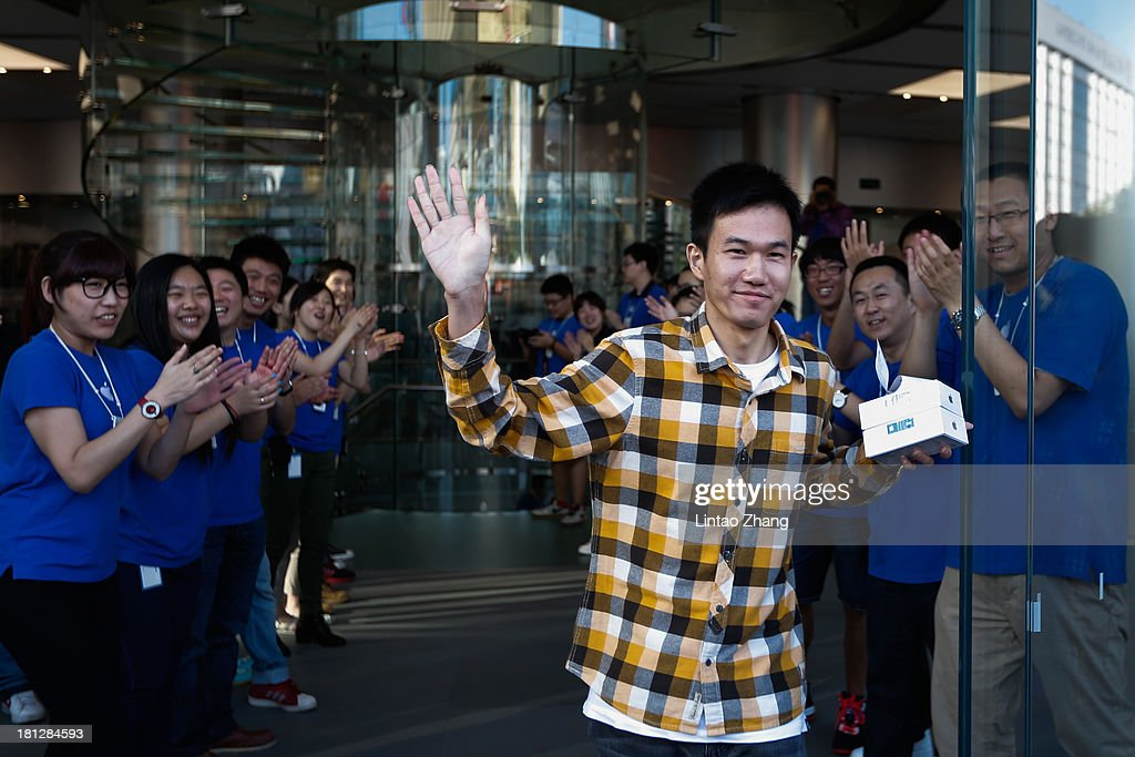 A customer celebrates buying two new iPhone 5s at the Wangfujing flagship store on September 20, 2013 in Beijing, China. Apple launched the new iPhone 5C model that will run iOS 7 is made from hard-coated polycarbonate and comes in various colors and the iPhone 5S that features fingerprint recognition security.
