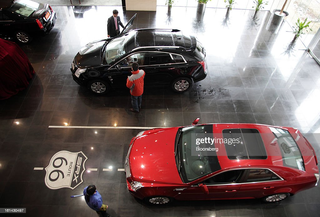 A customer, center, looks at a General Motors Co. Cadillac SRX supports utility vehicle (SUV), while a Cadillac CTS vehicle is displayed at a dealership in Shanghai, China, on Friday, Feb. 8, 2013. China's services industries grew at the fastest pace since August as gains in retailing and construction aid government efforts to drive a recovery in the world's second-biggest economy. Photographer: Tomohiro Ohsumi/Bloomberg via Getty Images