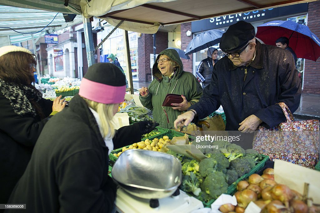 A customer, center, reacts as she speaks with a trader at a fruit and vegetable market stall in Guildford, U.K., on Friday, Dec. 14, 2012. Standard & Poor's lowered its outlook on Britain's top credit rating to negative, citing weak economic growth and a worsening debt profile. Photographer: Simon Dawson/Bloomberg via Getty Images