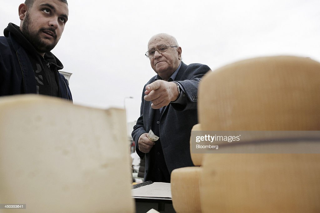 A customer, center, selects cheese from a stall at a farmers' market in Thessaloniki, Greece, on Saturday, Nov. 16, 2013. Greek Prime Minister Antonis Samaras, who survived a no-confidence vote on Nov. 11 with his parliamentary majority reduced to four, is trumpeting the first economic growth in seven years for 2014. Photographer: Konstantinos Tsakalidis/Bloomberg via Getty Images
