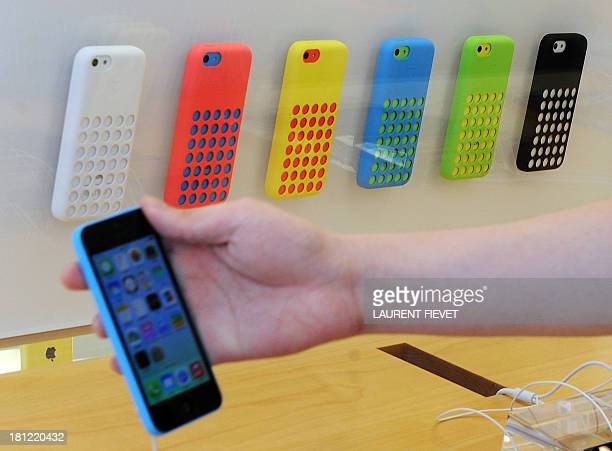 A customer checks a new iPhone 5c in front of a display of cases inside an Apple store in Hong Kong on September 20 2013 Apple acolytes got their...