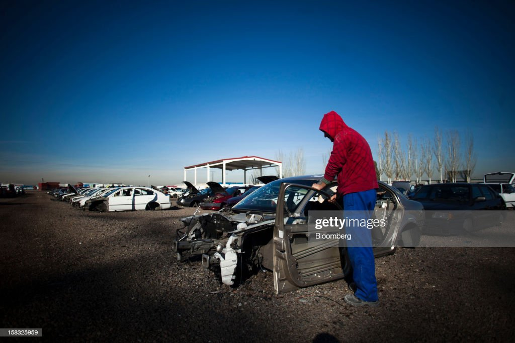 A customer checks a vehicle door in the yard of the Desguaces La Torre scrapyard in Madrid, Spain, on Thursday, Dec. 13, 2012. Spain has completed the debt sales it planned for this year and started raising funds for 2013, buying time for Prime Minister Mariano Rajoy as he decides whether to seek a European bailout. Photographer: Angel Navarrete/Bloomberg via Getty Images