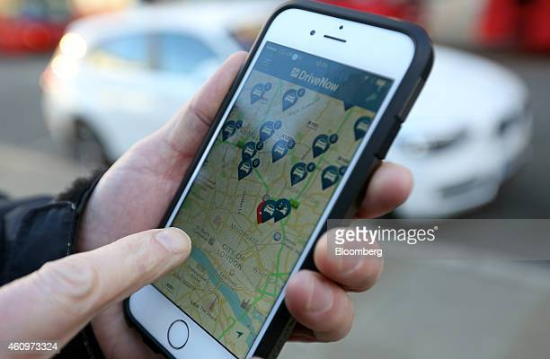 A customer checks an app on his smartphone for the location of a BMW 1 series automobile part of the DriveNow carsharing venture between Bayerische...