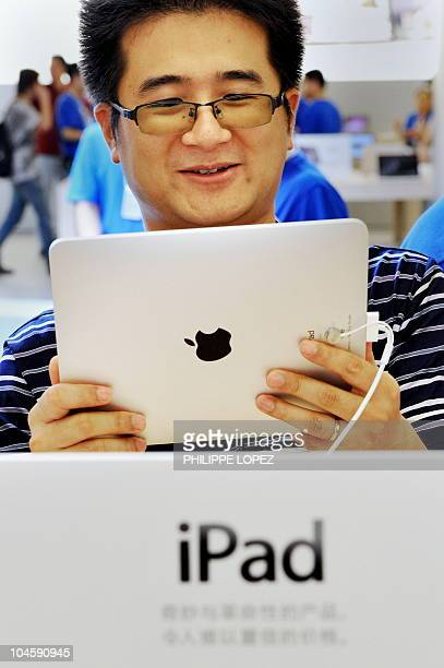 A customer checks an iPad at the Apple store in Shanghai on September 17 2010 Apple officially launched its iPad in China a surefire winner analysts...