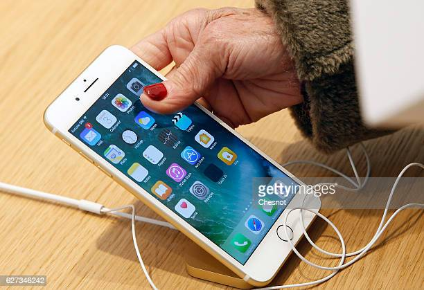A customer checks an iPhone 7 inside the new Apple store SaintGermain during the first opening day on December 03 2016 in Paris France This store...