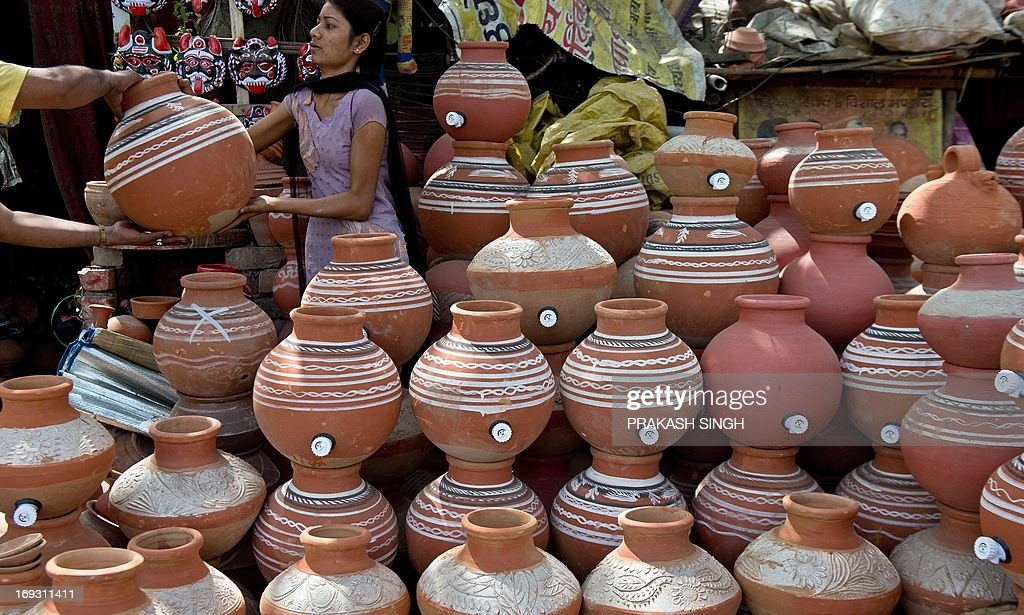 A customer checks earthen pots, used to store drinking water, in New Delhi on May 23, 2013. Heatwave conditions continued in the Indian capital, with temperatures registering a record high for the month of May at 45.6 degrees celsius. AFP PHOTO/ Prakash SINGH