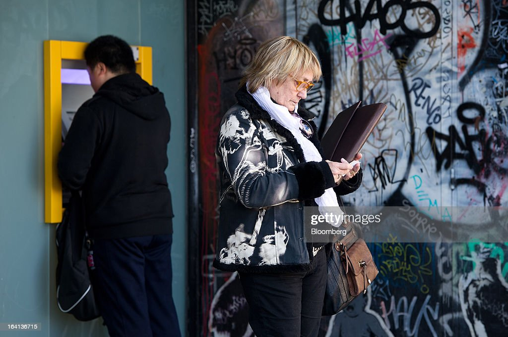 A customer checks her bank receipt after using an automated teller machine (ATM) outside a CaixaBank SA branch in Barcelona, Spain, on Wednesday, March 20, 2013. Officials from the troika of international creditors -- the ECB, the International Monetary Fund and the European Commission -- are in Cyprus discussing further capital controls and possibly extending a bank holiday to the end of the week, a European official familiar with the talks said on condition of anonymity because the discussions are confidential. Photographer: David Ramos/Bloomberg via Getty Images