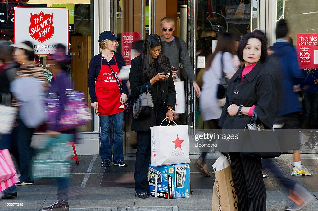 A customer checks her phone while holding shopping bags outside of the Westfield San Francisco Centre in San Francisco, California, U.S., on Friday, Nov. 23, 2012. To get shoppers to spend more than last year, retailers have continued to turn Black Friday, originally a one-day event after Thanksgiving, into a week's worth of deals and discounts. Photographer: David Paul Morris/Bloomberg via Getty Images