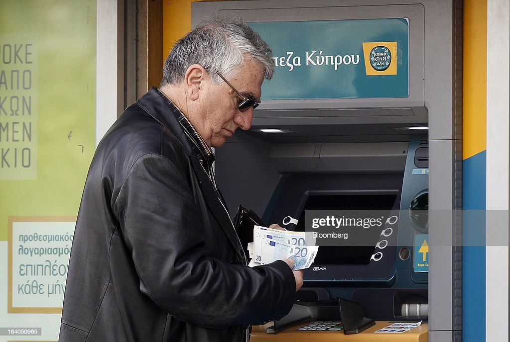 A customer checks his euro banknotes after withdrawing them from an automated teller machine (ATM) outside a closed bank branch at the headquarters of the Bank of Cyprus Plc in Athens, Greece, on Tuesday, March 19, 2013. Cyprus's passage of an unprecedented levy on bank deposits was in doubt as euro-area finance ministers responded to criticism of the measure by loosening their stance on how the money is raised. Photographer: Kostas Tsironis/Bloomberg via Getty Images