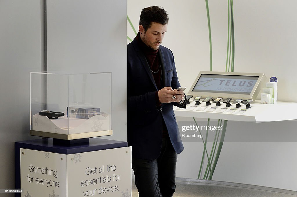 A customer checks his mobile device at a Telus Corp. learning center and store in Toronto, Ontario, Canada, on Wednesday, Feb. 13, 2013. Telus Corp. is scheduled to release earnings data on Feb. 15. Photographer: Aaron Harris/Bloomberg via Getty Images