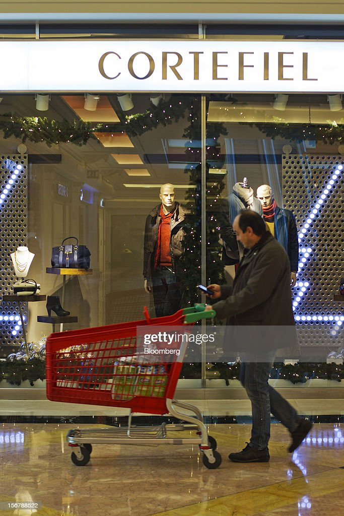 A customer checks his mobile phone while pushing a supermarket trolley past a Cortefiel SA store window in Majadahonda, near Madrid, Spain, on Tuesday, Nov. 20, 2012. Bank of Spain Governor Luis Maria Linde said the government risks missing its budget targets this year and next, adding to doubts on Prime Minister Mariano Rajoy's ability to cut the deficit amid a five-year slump. Photographer: Angel Navarrete/Bloomberg via Getty Images