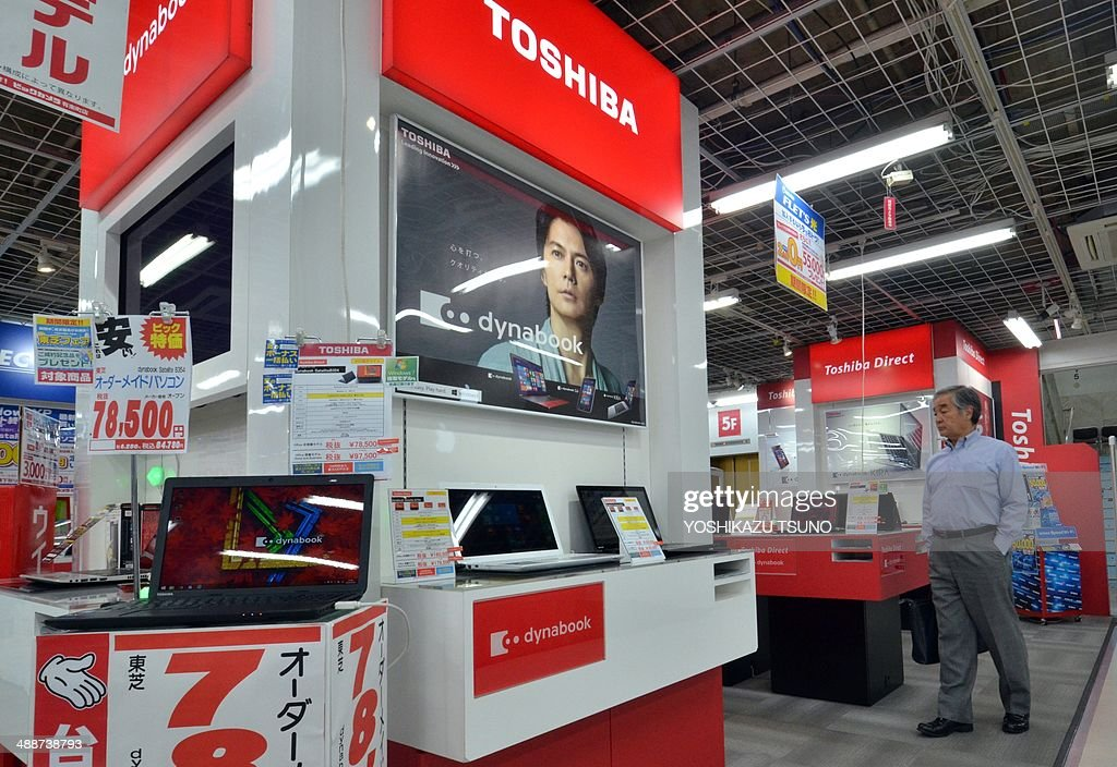A customer checks Japanese electronics giant Toshiba's notebook computers at an electric shop in Tokyo on May 8, 2014. Toshiba said its full-year net profit fell about 34 percent with one-off costs weighing on its bottom line as the Japanese firm reportedly eyes French giant Alstom's power-grid business. The fall in Toshiba's net earnings to 50.83 billion yen (500 million USD) in the fiscal year to March was chiefly due to the cost of exiting an optical disc drive business jointly run with South Korea's Samsung. AFP PHOTO / Yoshikazu TSUNO