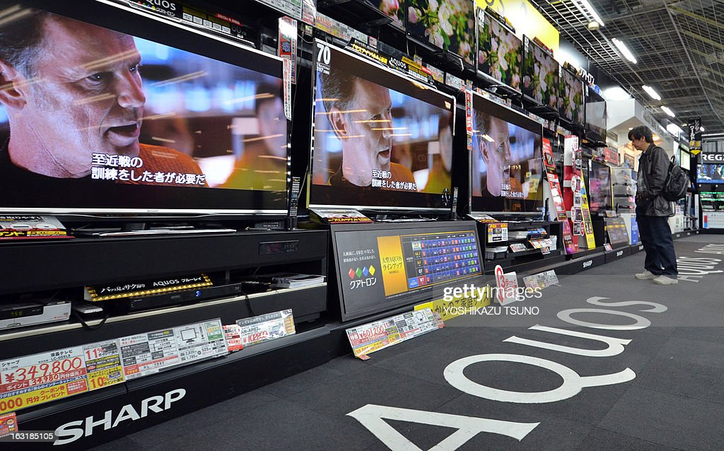 A customer checks LCD television sets by Japanese electronics maker Sharp at an electronics shop in Tokyo on March 6, 2013. Shares in embattled Sharp soared on March 6 after reports that South Korean rival Samsung would become its biggest foreign shareholder, highlighting the fading fortunes of Japan's electronics giants. The huge move was stoked by reports in Japan's leading Nikkei business daily and other media that Samsung was set to invest in Sharp to boost its access to screens used in its popular smartphones and tablet computers -- a sector where Sharp's technology is a world leader. AFP PHOTO / Yoshikazu TSUNO