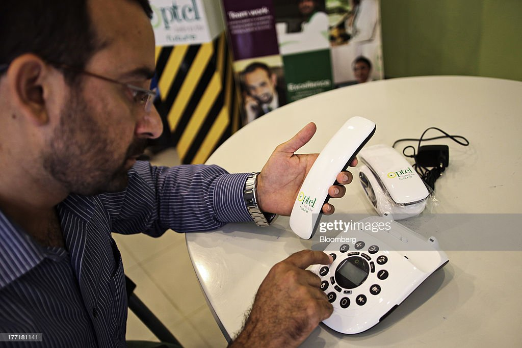 A customer checks the features of a telephone on sale at the Pakistan Telecommunications Co. (PTCL) sales and customer care center in Islamabad, Pakistan, on Wednesday, Aug. 21, 2013. Pakistan Telecommunication, the countrys biggest fixed-line phone-service provider, said second-half sales growth will at least match the pace of the previous six months as broadband demand increases. Photographer: Asad Zaidi/Bloomberg via Getty Images