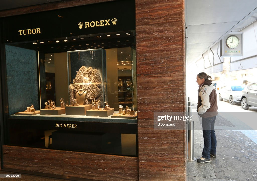 A customer checks the selection of luxury watches on display in the window of a watch store in the town of Davos, Switzerland, on Saturday, Jan. 19, 2013. Next week the business elite gather in the Swiss Alps for the 43rd annual meeting of the World Economic Forum in Davos, the five day event runs from Jan. 23-27. Photographer: Chris Ratcliffe/Bloomberg via Getty Images