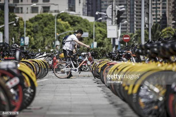 A customer chooses a BeijingMobikeTechnology Co bicycle from a designated parking space outside a subway station in Shanghai China on Thursday Sept...