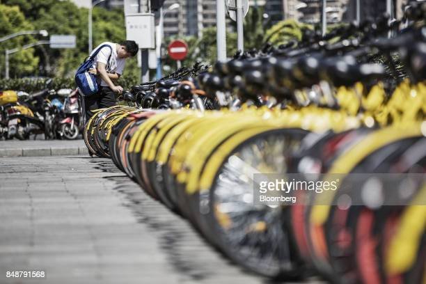 A customer chooses a bicycle from a designated parking space outside a subway station in Shanghai China on Thursday Sept 12 2017 Across Chinese...