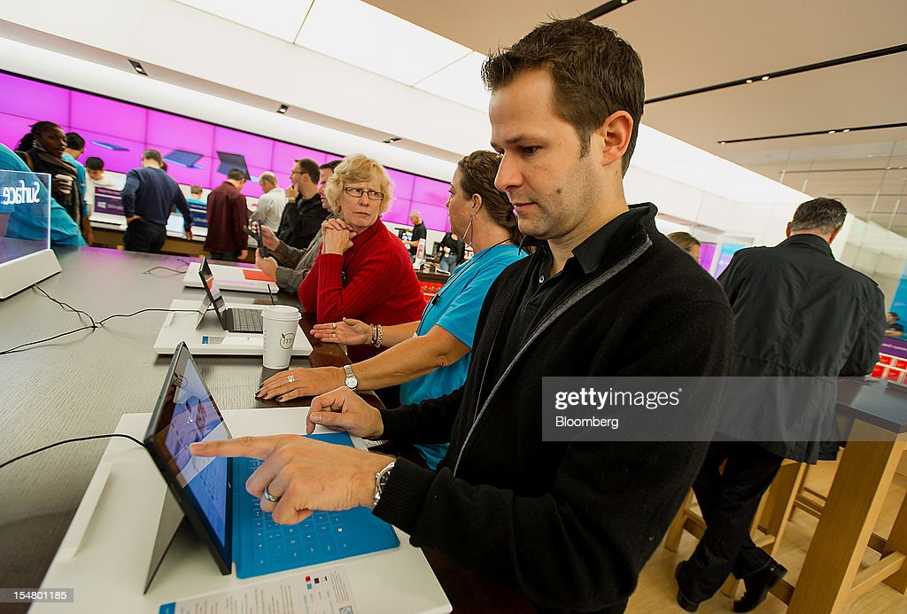 Customer Chris Johnson uses the Surface table computer at the opening of a Microsoft Corp. store in Bellevue, Washington, U.S., on Friday, Oct. 26, 2012. Microsoft Corp. introduced the biggest overhaul of its flagship Windows software in two decades, reflecting the rising stakes in its competition with Apple Inc. and Google Inc. for the loyalty of customers who are shunning personal computers and flocking to mobile devices. Photographer: Stuart Isett/Bloomberg via Getty Images