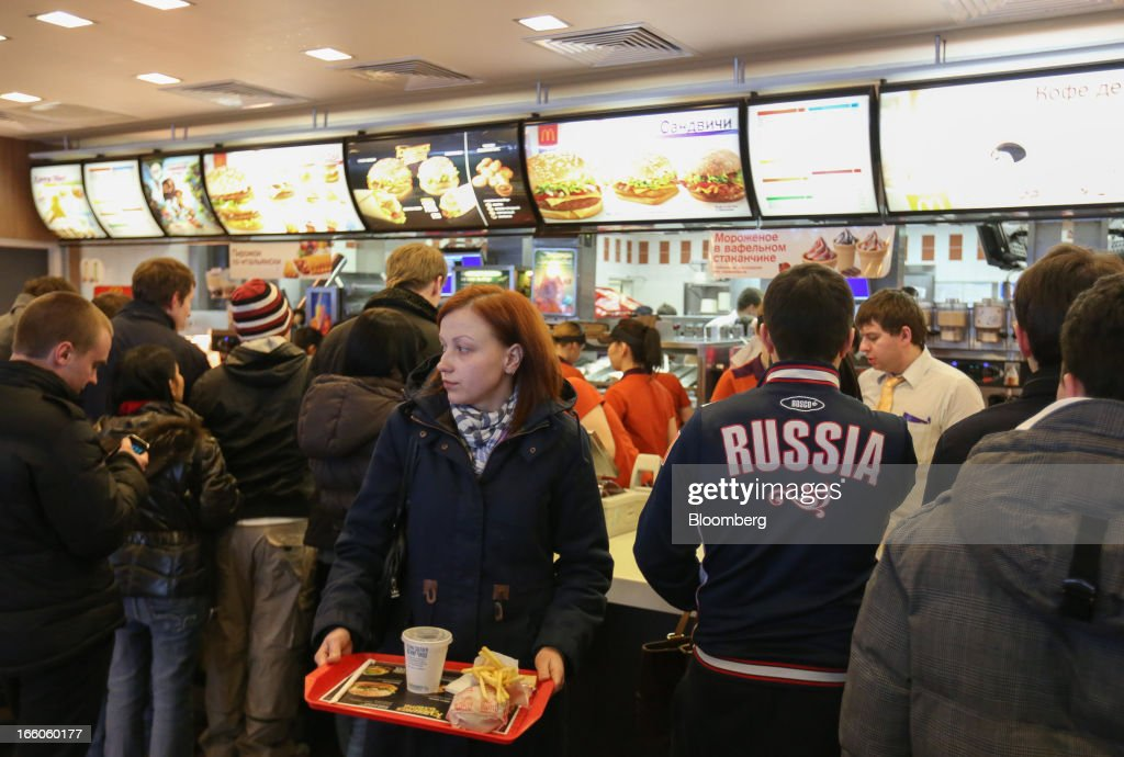 A customer collects a tray of food at the service counter of a McDonald's food restaurant in Moscow, Russia, on Sunday, April 7, 2013. McDonald's Corp., which virtually created the market for burgers and fries in the country and convinced Russians it's OK to eat with their hands, must fend off a growing challenge from rivals Burger King Worldwide Inc., Subway Restaurants, Yum! Brands Inc. and Wendy's Co. Photographer: Andrey Rudakov/Bloomberg via Getty Images