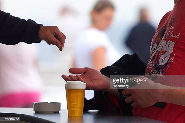 A customer collects change after purchasing a plastic cup of beer in Binz on Ruegen Island Germany on Saturday Aug 10 2013 Chancellor Angela Merkel's...