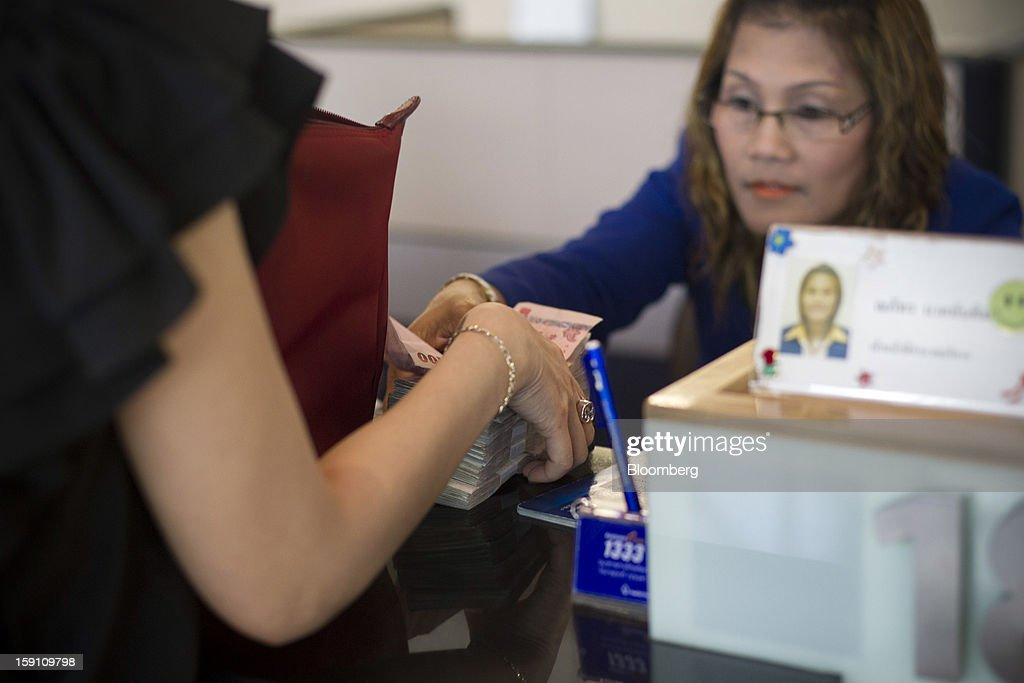 A customer collects Thai Baht banknotes at the Bangkok Bank Pcl. headquarters in Bangkok, Thailand, on Tuesday, Jan. 8, 2013. Thailand's economy may have expanded 5.7 percent in 2012 and will grow 5 percent in 2013, the finance ministry said on Dec. 26. Photographer: Brent Lewin/Bloomberg via Getty Images