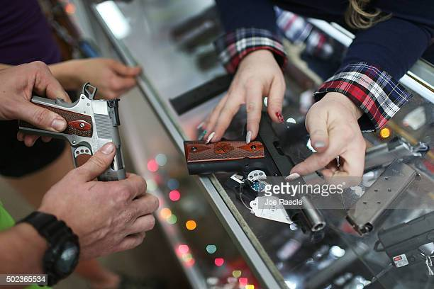 A customer compares handguns before buying one as a Christmas present at the National Armory gun store on December 23 2015 in Pompano Beach Florida...
