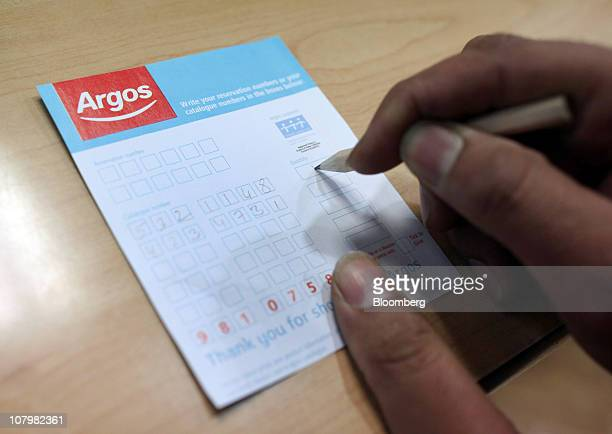 A customer completes an order form at an Argos store operated by Home Retail Group Plc in London UK on Tuesday Jan 11 2011 UK retail sales fell last...