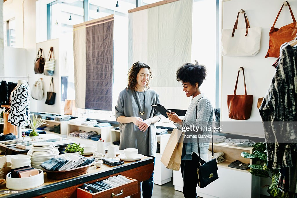 Customer completing transaction on digital tablet : Stock Photo